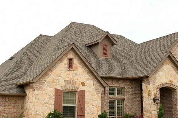 A stone house is pictured with a brand new roof