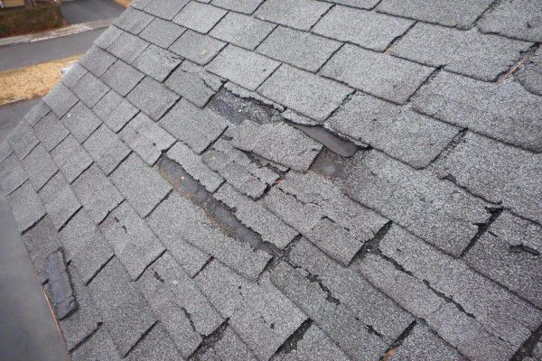 A roof with shingles that have been cracked and broken by hail