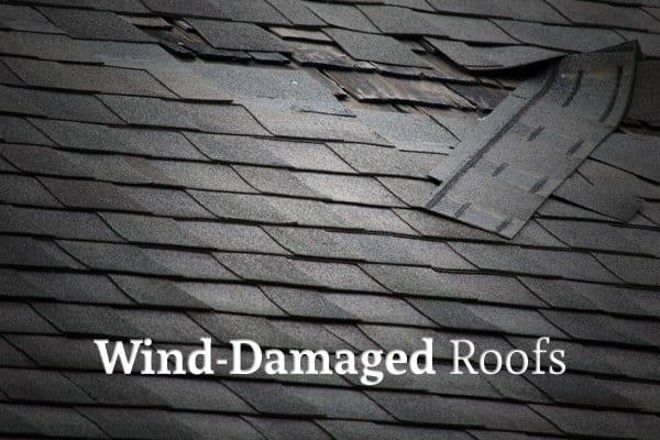 "A roof with some of the shingles blown off with the words ""Wind-Damaged Roofs"""