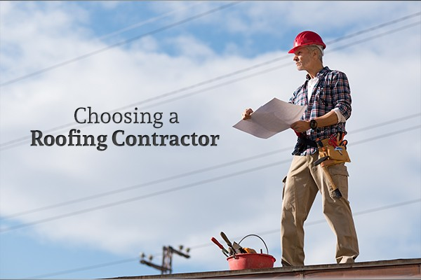 "A roofing contractor with a sheet of paper and his tools stands atop a roof beside the words ""Choosing a Roofing Contractor"""