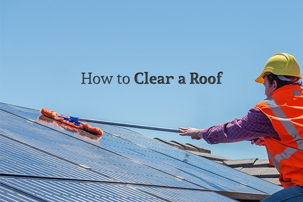 """A worker in a reflective vest with a hard hat sweeping off a roof under the words """"How to Clear a Roof"""""""