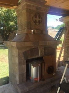 New outdoor fireplace installed with a covered patio