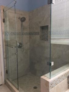 Newly remodeled bathroom with new tile and enclosed glass shower doors