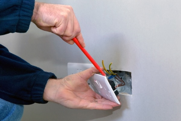 A man fixing the wiring for an outlet.
