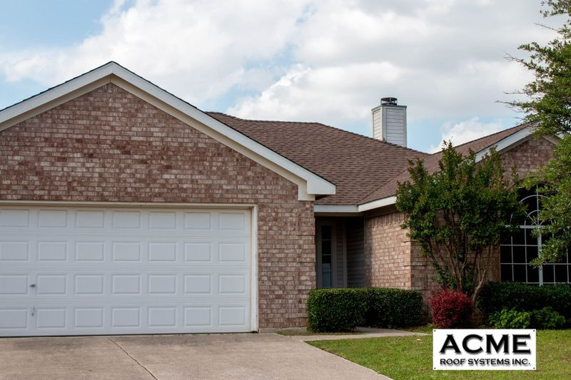 Street view of a house with a new roof with the Acme Roof Systems logo.