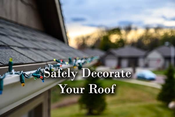 A roof with beautiful Christmas lights on the gutter along with the words, safely decorate your roof.